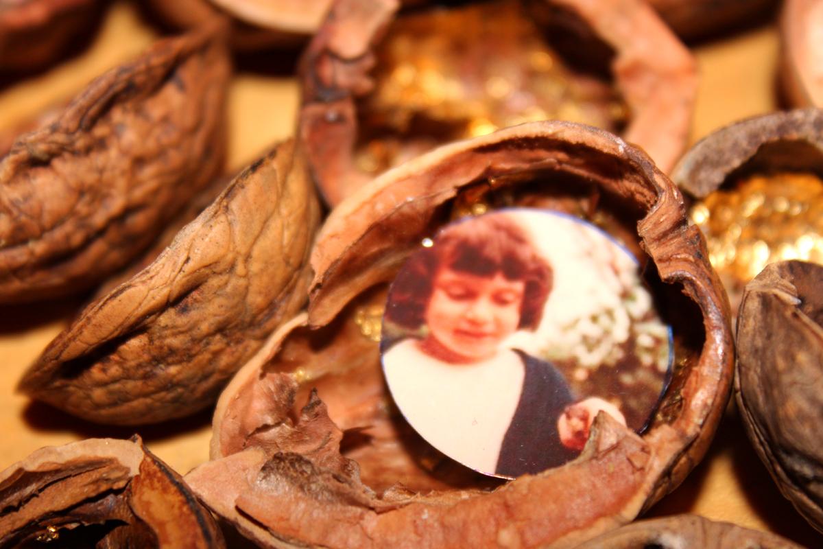 Naufragio gusci di noce dorati con foto istallazione particolare bambina sfocata