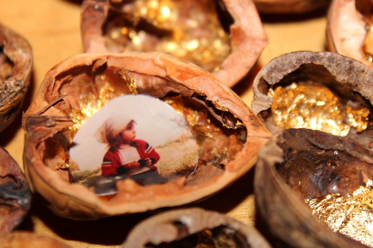 naufragio gusci di noci dorati con fotografie particolare bambina seduta